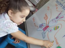 young girl drawing on a board